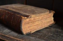 Vieux livre attaché en cuir s'étendant sur une étagère en bois poussiéreuse Photographie stock libre de droits