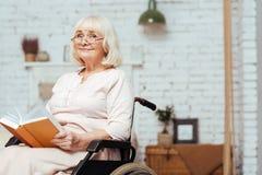 Vieux livre de lecture handicapé satisfait de dame à la maison Photo libre de droits