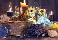 Vieux livre de sorcière avec les fleurs de lavande, le cristal et les bougies de mal photographie stock