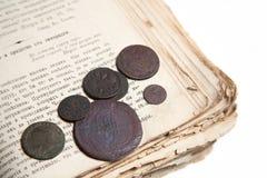 Vieux livre et pièces de monnaie Photo stock