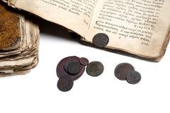Vieux livre et pièces de monnaie Images stock