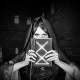Vieux livre magique de belle jeune sorcière de Halloween Photographie stock