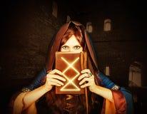 Vieux livre magique de belle jeune sorcière de Halloween Photos stock