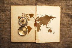 Vieux livre ouvert avec la carte de boussole et du monde Images stock
