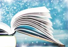 Vieux livre ouvert avec la lumière et les étoiles filantes magiques Images libres de droits