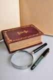 Vieux livre, stylo et magnifie photographie stock