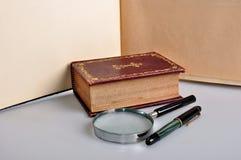 Vieux livre, stylo et magnifie image stock