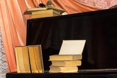 Vieux livres étendus sur le piano images stock