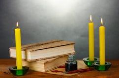 Vieux livres, défilements, encrier encastré de crayon lecteur d'encre et bougies Images stock