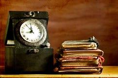 Vieux livres d'horloge et de vintage sur le fond grunge Image libre de droits