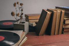 Vieux livres de cru, disques vinyle et une fleur sèche dans un vase concret photographie stock