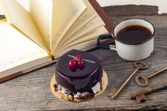 Vieux livres de vintage, tasse de thé, gâteau et clés sur la table en bois rustique Photographie stock