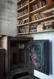Vieux livres et un coffre-fort en acier dans une étagère abandonnée d'école photographie stock