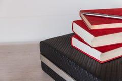 Vieux livres rouges sur un bureau avec un fond blanc Image stock