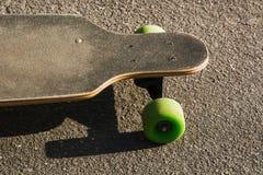 Vieux longboard utilisé au sol Planche à roulettes noire sur une route goudronnée vide Fin vers le haut image libre de droits