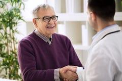 Vieux mâle en bonne santé heureux de sourire secouant avec le docteur Image libre de droits