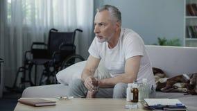 Vieux mâle handicapé s'asseyant sur le divan et prenant des pilules, la solitude et la tristesse Photos stock