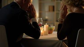 Vieux ménages mariés priant avant le repas, se reposant à la table, dîner de thanksgiving banque de vidéos