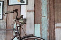 Vieux maigre de bicyclette sur le mur en bois âgé image libre de droits