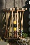Vieux maillets de croquet bien-utilisés dans un support se penchant contre un mur en bois photo libre de droits
