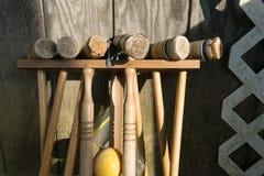 Vieux maillets de croquet bien-utilisés dans un support se penchant contre un mur en bois, tir moyen photos libres de droits