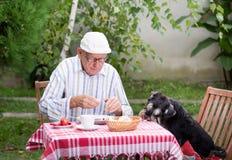 Vieux mangeur d'hommes dans le jardin avec le chien Images stock