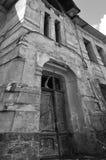 vieux manoir abandonné avec le plâtre moitié-peint dans des tons noirs et blancs Image stock