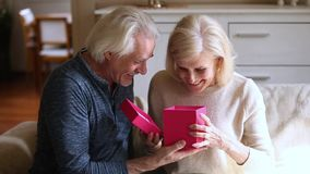 Vieux mari de soin donnant le boîte-cadeau à l'épouse mûre enthousiaste clips vidéos