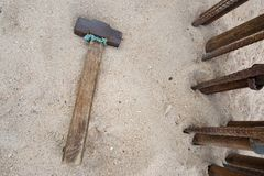Vieux marteau avec une poignée en bois sur le fond de plage de sable image stock