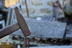 Vieux marteau martelant un clou dans un conseil en bois Photographie stock libre de droits