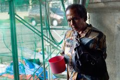Vieux mendiant masculin aveugle tenant l'aumône de recherche de plongeur de l'eau aux ruines portailes d'église photo stock