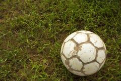 Vieux mensonges blancs minables de ballon de football sur un fond brouillé d'herbe verte photo libre de droits