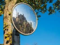 Vieux miroir en verre convexe souillé de sécurité routière au-dessus d'arbre avec la réflexion de maison dans le village anglais photos libres de droits