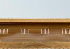 Vieux modèle brun de toit de tuiles d'argile avec de petites fenêtres sur wal en bois Photographie stock