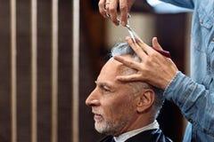 Vieux monsieur pendant la coupe de cheveux dans le raseur-coiffeur Image libre de droits