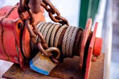 Vieux moteur en acier rouge industriel rouillé de treuil avec le câble, la chaîne et le cadenas Image libre de droits