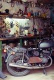 Vieux moto, équipement et outils sur le bureau dans le garage Photos stock