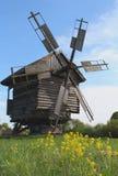 Vieux moulin à vent en bois et fleurs jaunes Photo stock