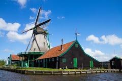 Vieux moulin à vent néerlandais au-dessus des eaux de rivière Images stock