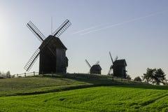 Vieux moulins à vent et traînées polonais des avions volant dans le ciel, Lednogora Images libres de droits