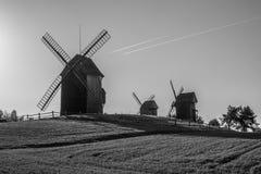 Vieux moulins à vent et traînées polonais des avions volant dans le ciel, Lednogora Image libre de droits