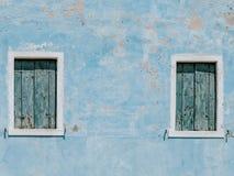 Vieux mur bleu de maison avec deux fenêtres en bois photos stock