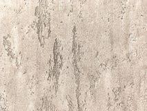 Vieux mur brun clair couvert de plâtre inégal minable Texture de la surface de pierre de bronze de vintage, plan rapproché images stock