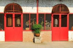 Vieux mur de briques avec les portes et les fenêtres et la plante en pot rouges Photographie stock