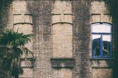Vieux mur de briques avec trois fenêtres, deux faux, une avec le cadre en verre et bleu de couleur images stock