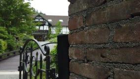 Vieux mur de briques et barrière rouges avec le fond de maison brouillé de pays banque de vidéos
