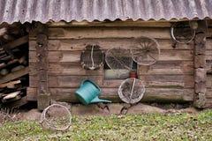 Vieux mur en bois grunge de maison avec des outils agricoles Photographie stock libre de droits