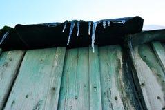 Vieux mur en bois vert, toit avec des glaçons et neige blanche sur le dessus, vue de la terre sur le fond clair bleu de ciel, hiv photos libres de droits