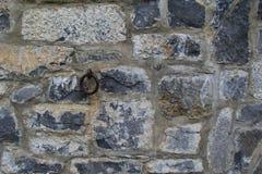Vieux mur en pierre avec le grand crochet rouillé Image stock