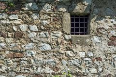Vieux mur en pierre d'âge foncé et petite fenêtre de cellules de prison avec des barres Images stock
